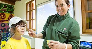 Operatirice dell'Ente Foreste Sardegna che trucca una bambina per la giornata del benessere psicologico a Mont'Arrubiu