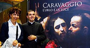 """Don Elenio Abis e la Professoressa Alessandra pasolina in posa con nello sfondo il quadro di Caravaggio, locandina della mostra """"L'Urlo e la Luce"""""""