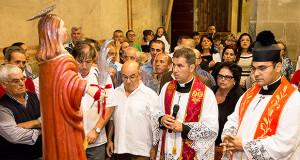 Foto del Parroco di Dolianova e dei fedeli rivolti in preghiera al Patrono San Pantaelo di Dlianova.